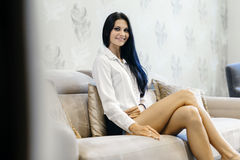 Elegant and sexy woman sitting on a sofa in a luxurious room Royalty Free Stock Image