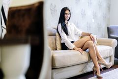 Elegant and sexy woman sitting on a sofa in a luxurious room Royalty Free Stock Photography