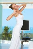 Elegant shapely woman stretching. Shapely beautiful woman in a flowing white outfit stretching in a modern glass fronted living room overlooking the ocean Stock Images