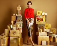 Free Elegant Shopper Woman Among 2 Piles Of Golden Gifts Stock Photos - 137222633