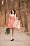 Elegant shopper woman walking in park after shopping Royalty Free Stock Images