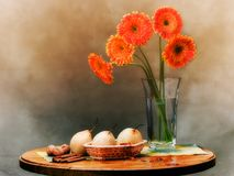 Elegant sill life with orange flowers. Pears, nuts and amber Stock Photos