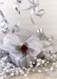 Elegant silver gift. Elegantly wrapped gift surrounded by sliver ribbons and pearls stock photography