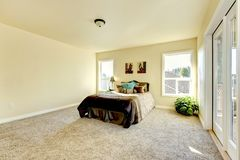 Elegant and simple bedroom in milky tones with beige carpet. Royalty Free Stock Photos