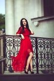 Elegant sinnlig sexig ung kvinna i den röda klänningen som poserar nära en ledstång Royaltyfria Foton