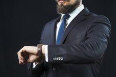 Elegant skäggig man i dräkten som ser hans klocka Arkivfoto