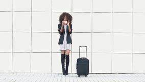 Elegant slim african american woman with luggage makes selfie at the airport. White textured wall background. Getting stock video