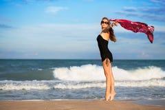 Elegant slim woman. With pink pareo posing on the beach stock photos