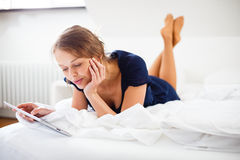 Elegant, smart, young woman using her tablet computer in bed Royalty Free Stock Photos