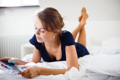 Elegant, smart, young woman using her tablet computer in bed Stock Photo