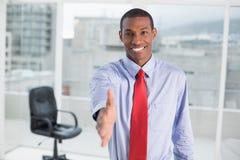 Elegant smiling Afro businessman offering handshake at office Stock Photos