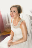 Elegant smiling bride posing on chair at bedroom Stock Photography