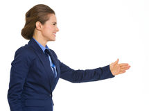 Elegant, smiling business woman in profile going to shake hands Royalty Free Stock Photos