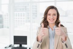 Elegant smiling businesswoman gesturing thumbs up in office Royalty Free Stock Images