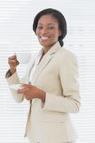 Elegant smiling businesswoman with tea cup in office Stock Photo