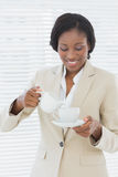 Elegant smiling businesswoman with tea cup in office Royalty Free Stock Photos