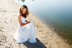 Elegant smiling girl bride in a white dress on a sandy river beach Royalty Free Stock Photos