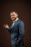 Elegant smiling man with beard holding smoking pipe. Portrait of handsome confident man in suit holding smoking pipe against of brown background.Isolated Stock Images