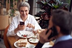 Elegant smiling woman in cafe checking smartphone. Enjoyable meetings. Close up portrait of smiling elegant aged lady checking mobile phone while in restaurant stock image