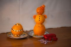 Elegant snowman from tangerines in a red cap from carrots in a saucer and a red toad from bell pepper on a wooden table stock images