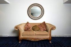 Elegant soffa mot väggen med spegeln royaltyfria foton