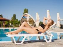 Elegant, sportief meisje in een bikini op een chaise-longue op een toevluchtachtergrond Ontspannend concept De ruimte van het exe Stock Foto's