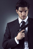 Elegant spy portrait. Elegant and handsome spy posing with gun in hand. Grey backdrop portrait Stock Images