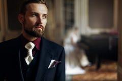 Elegant stilfull stilig brudgum som lyssnar till hans ursnygga brud p Arkivbild