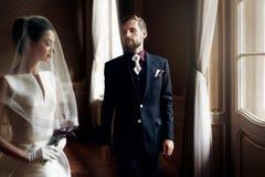 Elegant stilfull stilig brudgum som ser den ursnygga bruden, standi arkivbild