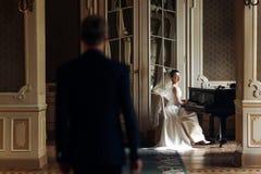 Elegant stilfull stilig brudgum som ser hans ursnygga brudplommoner royaltyfria bilder