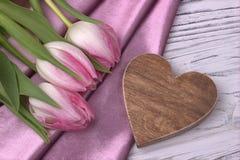 Elegant stilleben med rosa tyg för sken för tulpanblommaros och hjärtaformtecken på vit träbakgrund Kvinnas dag 8 mars Royaltyfri Bild