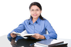 Elegant student. A female student or teacher perhaps, is posing while holding book. The glass desk was set to be minimalist with only some books on it Stock Photos