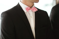 Elegant and stylish best men in black suits and pink bowties clo Stock Images