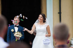 Elegant stylish brunette bride and groom throwing candies on the Stock Images