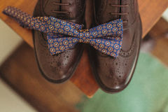 Elegant stylish dark male accessories on wooden background. Top view of bow-tie and shoes Stock Photos