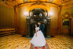 Elegant stylish groom dipping his charming wife, posing in rich interior of old classic mansion Stock Images
