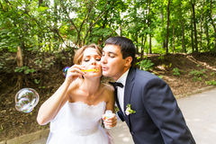 Elegant stylish groom and happy gorgeous  bride have fun with bubble blower outdoors in park Stock Images