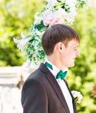 Elegant stylish groom having wedding ceremony on the background of arch Stock Images