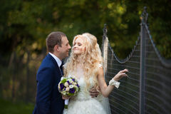 Elegant stylish groom with his happy gorgeous blonde bride on th Stock Images