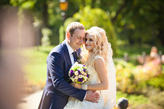 Elegant stylish groom with his happy gorgeous blonde bride on th Royalty Free Stock Photography