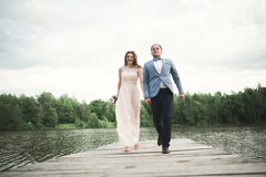 Elegant stylish groom with his happy gorgeous brunette bride on the background of a lake Royalty Free Stock Photo