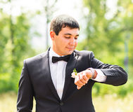 Elegant stylish groom waiting his brite and looks at watch Stock Photography