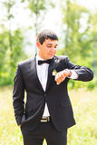 Elegant stylish groom waiting his brite and looks at watch Royalty Free Stock Photos