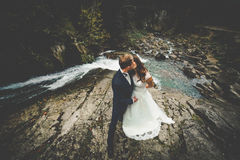 Elegant stylish happy brunette bride and gorgeous groom on the b. Ackground of a beautiful waterfall in the mountains stock photos