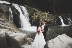 Elegant stylish happy brunette bride and gorgeous groom on the background of a beautiful river in the mountains.  stock images