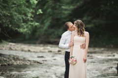 Elegant stylish happy brunette bride and gorgeous groom on the background of a beautiful waterfall in the mountains Royalty Free Stock Photo