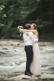 Elegant stylish happy brunette bride and gorgeous groom on the background of a beautiful waterfall in the mountains Royalty Free Stock Photography