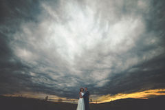 Elegant stylish happy brunette bride and gorgeous groom at the s. Unset on the background of fall mountains royalty free stock photo