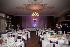 Elegant and stylish purple color wedding reception at luxury restaurant: tables Stock Photos