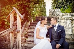 Elegant stylish young bride and groom sitting on the stairs in the park Stock Photo